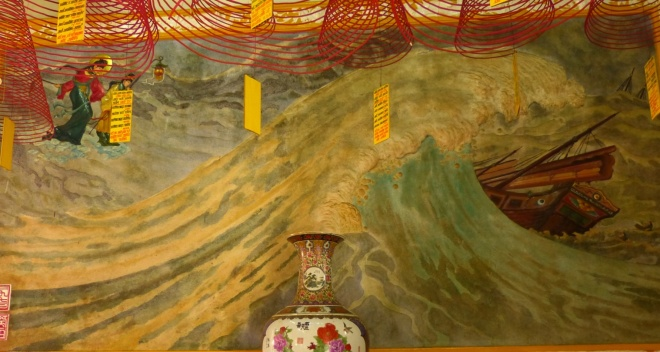 Painting of the sea goddess, under the incense coils and behind the vase.