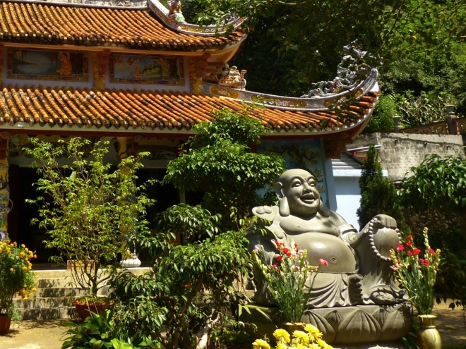 "At the top of the first ""staircase"", smiling Buddha (happiness), with a fat belly (prosperity) and long ears (longevity)"